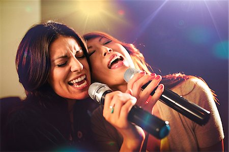 687-07066277 © Masterfile Royalty-Free Model Release: Yes Property Release: No Two women singing karaoke.
